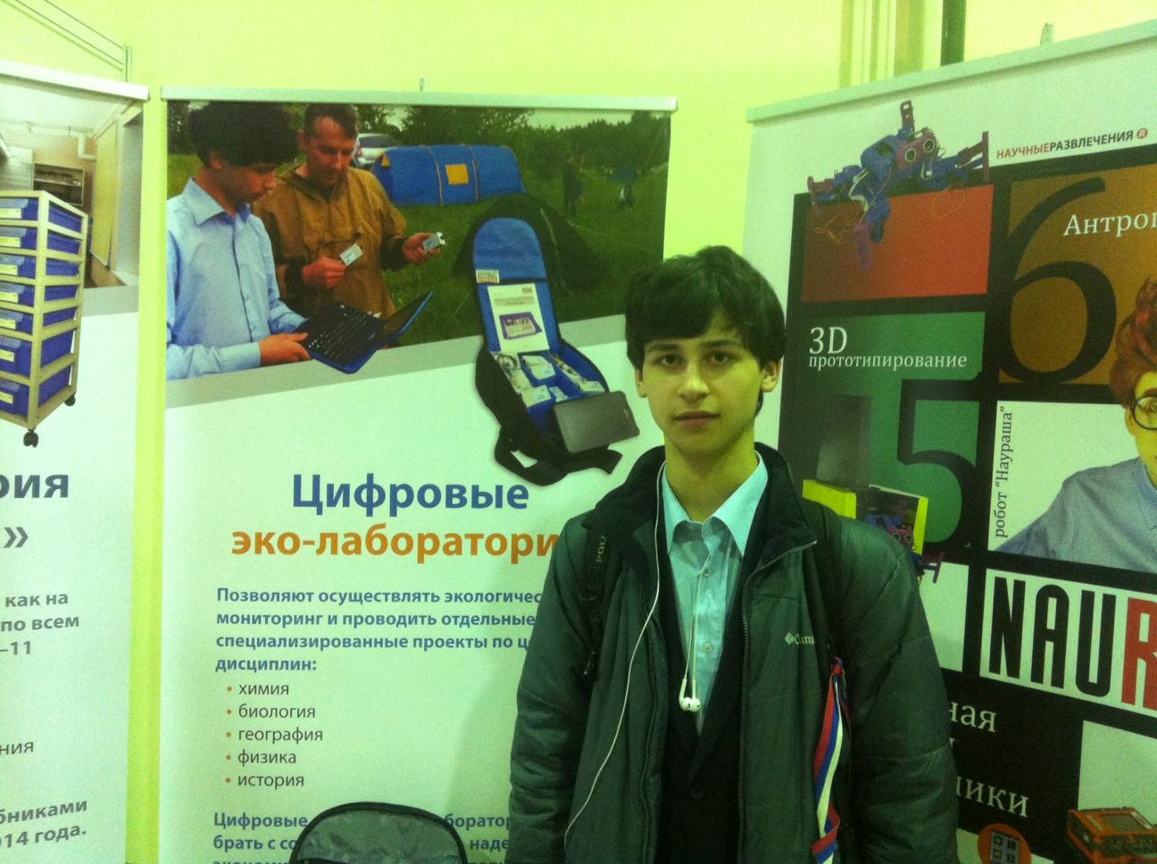 Никита Самойлов около плаката, на котором фото нашей школьной экологической экспедиции 2014 года