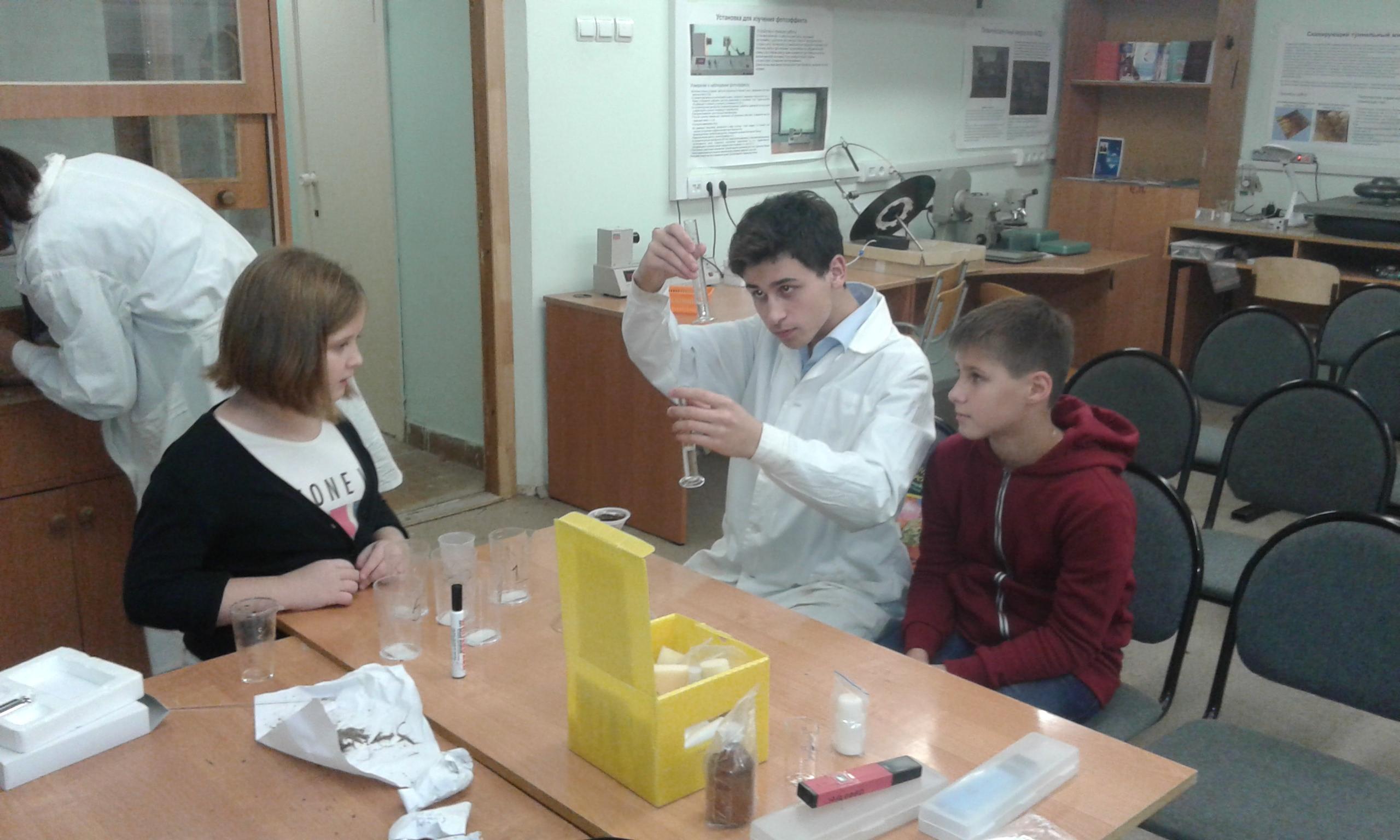 Никита Самойлов обучает ребят проведению биологических экспериментов