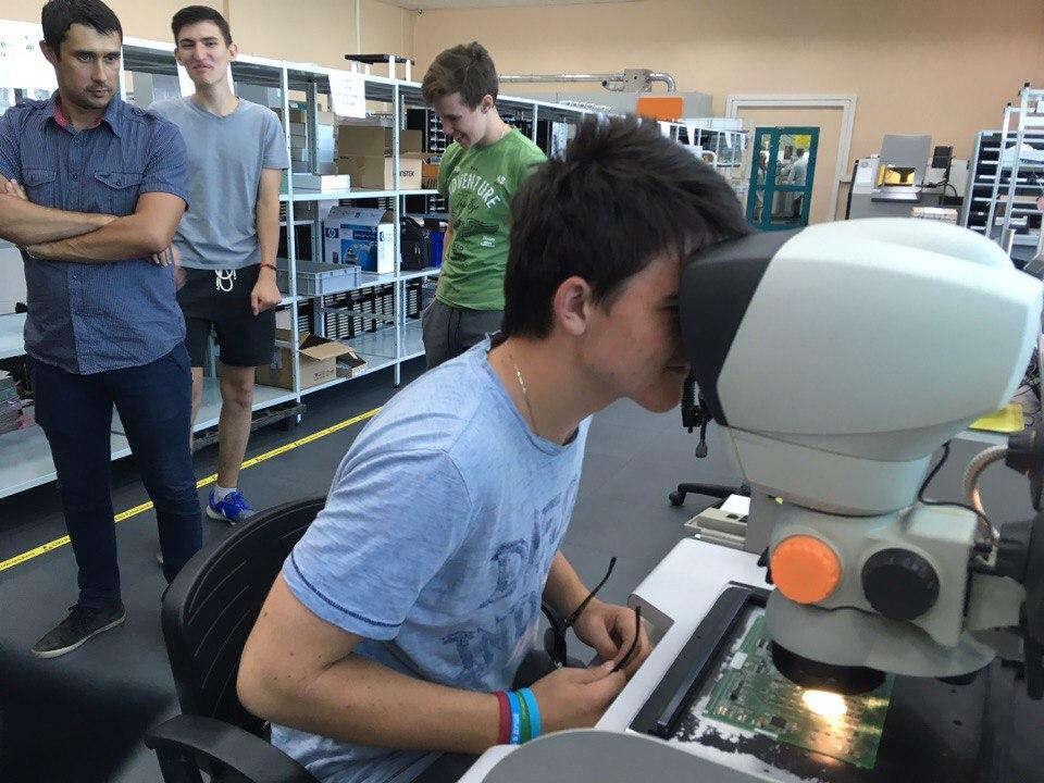 Юный исследователь Андрей изучает качество пайки на плате
